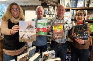 Four adults holding up books and smiling